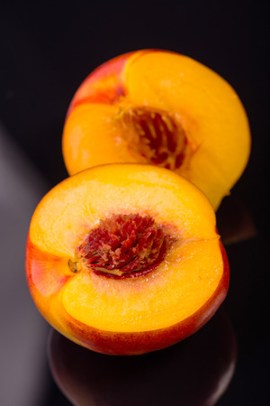 vitreous: Two halves of wonderful delicious nectarine lying on the black vitreous surface