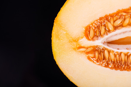 vitreous: Two halves of the wonderful ripe melon lying on the black vitreous surface