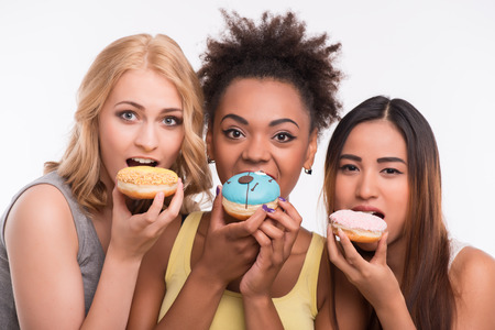 tolerate: Half-length portrait of three beautiful tempting girls wearing colorful T-shirts eating bright delicious doughnuts. Isolated on white background