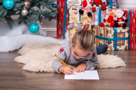 letter x: Selective focus on the pretty little fair-haired girl wearing warm sweater and jeans lying on the floor near the Christmas tree writing very diligently something Stock Photo