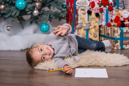 Selective focus on the pretty little fair-haired girl wearing warm sweater and jeans lying on the floor near the Christmas tree laughing having fun photo