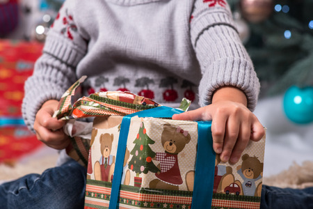 Selective focus on the little girl sitting on the floor near Christmas presents wearing warm sweater unpacking her desirable present photo