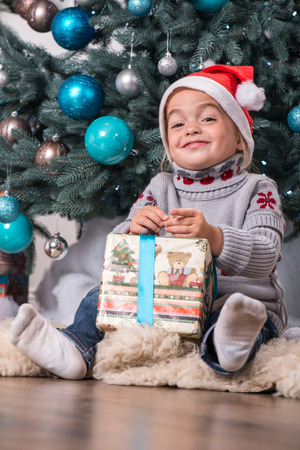 Half-length portrait of the little cute fair-haired smiling girl sitting on the floor near Christmas presents wearing warm sweater and red cap of Santa Claus unpacking her nice present photo
