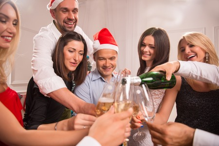 each year: Half-length portrait of the company of happy young friends standing in a circle pouring the champagne greeting each other with the New Year