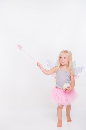 conjuring: Full-length portrait of little fair-haired lovely smiling girl wearing pretty grey vest pink skirt and white wings standing conjuring over someone. Isolated on white background Stock Photo