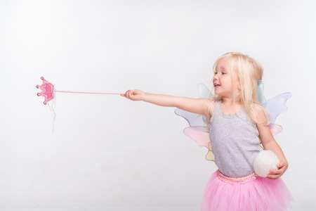 conjuring: Half-length portrait of little fair-haired lovely smiling girl wearing pretty grey vest pink skirt and white wings standing aside conjuring over someone. Isolated on white background