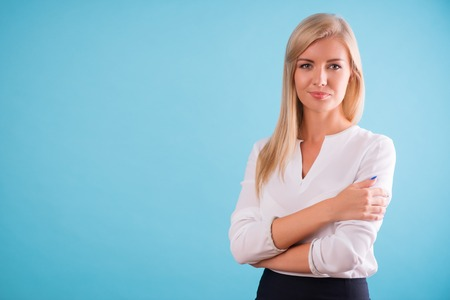 portrait: Half-length portrait of beautiful smiling blonde wearing white classic blouse standing aside cross-armed looking at us. Isolated on blue background