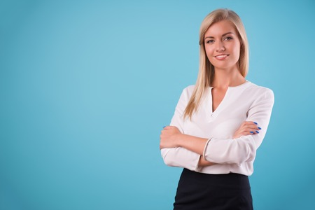come up to: Half-length portrait of beautiful smiling blonde wearing white classic blouse standing aside cross-armed looking at us. Isolated on blue background