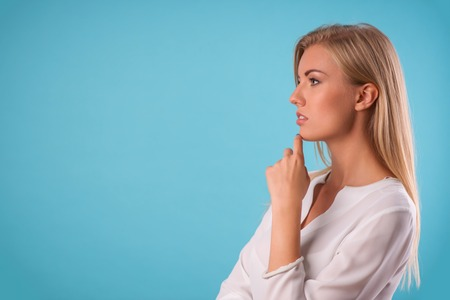 Half-length portrait of beautiful thoughtful blonde wearing white classic blouse standing aside recollecting something very important. Isolated on blue background photo