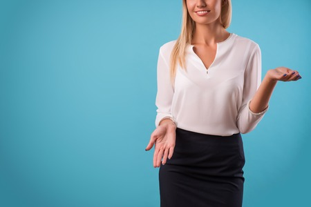 come up: Half-length portrait of beautiful smiling blonde wearing white classic blouse and black skirt standing pointing out something looking at us. Isolated on blue background