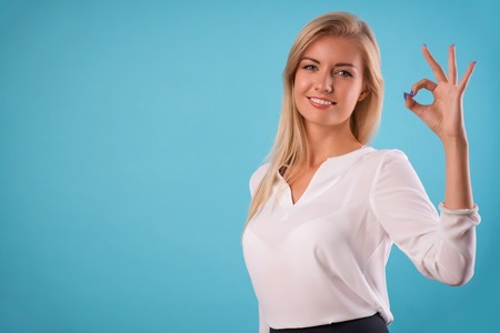 come up to: Half-length portrait of beautiful smiling blonde wearing white classic blouse and black skirt standing showing that everything will be ok. Isolated on blue background