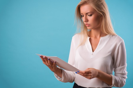 come up: Half-length portrait of beautiful business lady wearing white classic blouse standing aside looking at the white sheet of paper for copy place. Isolated on blue background