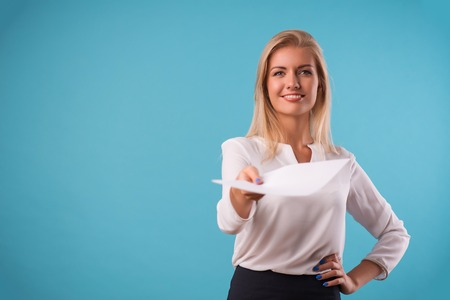 come up: Half-length portrait of beautiful business lady wearing white classic blouse standing giving us the white sheet of paper for copy place. Isolated on blue background