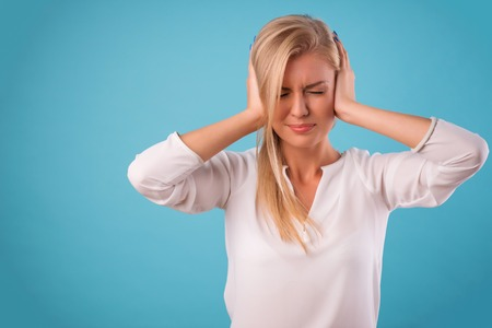 put up: Half-length portrait of beautiful tired blonde wearing white classic blouse and black skirt standing closing her ears cannot put up with this noise. Isolated on blue background