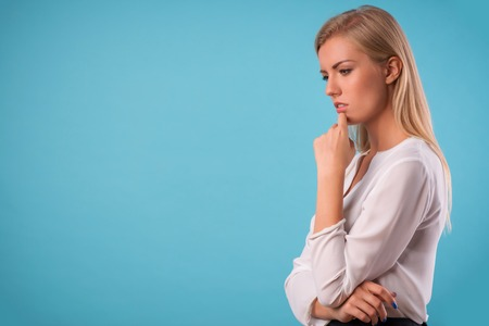 Half-length portrait of beautiful thoughtful blonde wearing white classic blouse and black skirt standing aside Isolated on blue background photo