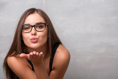 girl in shorts: Half-length portrait of smiling dark-haired young woman in the eyeglasses wearing black vest sending us a blowing kiss Stock Photo