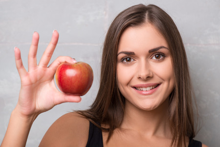 suggested: Half-length portrait of smiling dark-haired young woman wearing black vest holding very delicious ripe apple suggested us to taste it