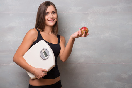 electronic balance: Half-length portrait of lovely smiling dark-haired young woman wearing black vest standing aside holding in one hand very delicious ripe apple and in another electronic balance