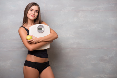 electronic balance: Half-length portrait of lovely smiling dark-haired young woman wearing black vest and shorts hugging very delicious ripe apple and electronic balance Stock Photo