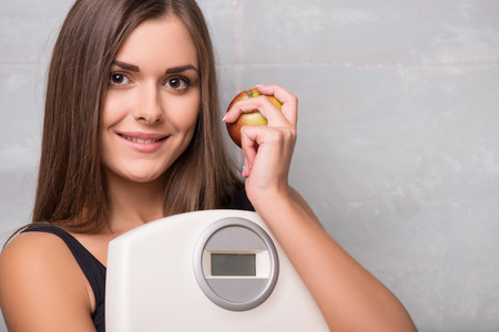 electronic balance: Half-length portrait of lovely smiling dark -haired young woman wearing black vest and shorts hugging very delicious ripe apple and electronic balance