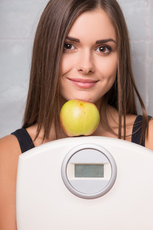 electronic balance: Half-length portrait of lovely smiling dark -haired young woman wearing black vest hugging electronic balance with very delicious ripe apple standing on it Stock Photo