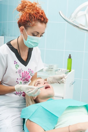 Half-length portrait of young dentist wearing medical mask treated teeth of her new young patient sitting on the dentist chair photo