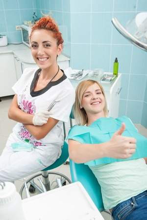 Half-length portrait of young fair-haired lovely smiling girl sitting together with the dentist showing that there is nothing better than healthy teeth photo