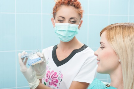 Half-length portrait of young fair-haired lovely smiling girl sitting on the dentist chair looking at the doctor wearing a mask which is showing her false tooth photo