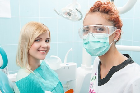 Half-length portrait of young smiling patient looking at us together with the doctor wearing medical mask and special eyeglasses photo