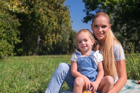 Selective focus on beautiful smiling mom and her lovely daughter wearing jeans sitting on the open air having a picnic photo