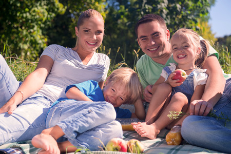 Portrait of happy young family consisted of mom daddy son and little daughter laughing having a picnic photo