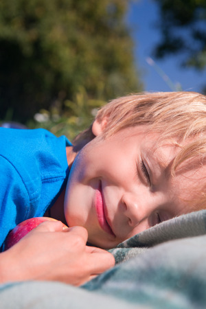 Selective focus on little fair-haired boy wearing blue T-shirt lying on the nice plaid hugging an apple screwing up his eyes from sun photo