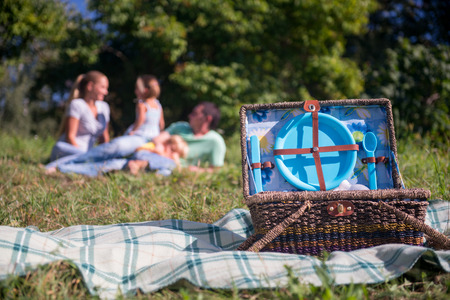 holidays family: Selective focus on the great wicker basket for picnic standing on the plaid on grass with blue crockery in it. Happy family lying on background Stock Photo