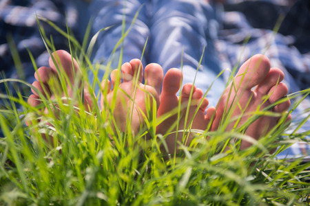picnicking: Someones bare feet lying on the grass