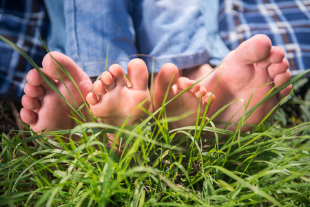 father in law: Someones bare feet lying on the grass