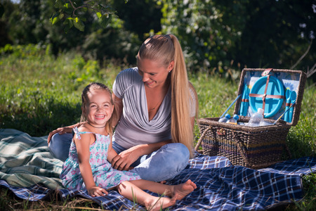 Selective focus on happy young fair-haired mother with her lovely smiling daughter sitting on the plaid near the wonderful wicker basket for picnic talking about something having fun photo