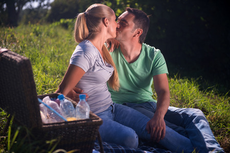 Selective focus on the lovely couple wearing T-shirts and jeans sitting on the plaid near the wicker basket for picnic looking at each other kissing photo