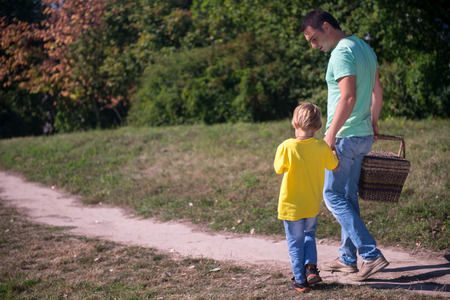 Selective focus on the father and son wearing T-shirts and jeans coming back from the picnic holding a wicker basket photo