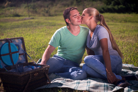 Full-length portrait of lovely couple wearing T-shirts and jeans sitting on the plaid near the wicker basket for picnic looking at each other with love photo