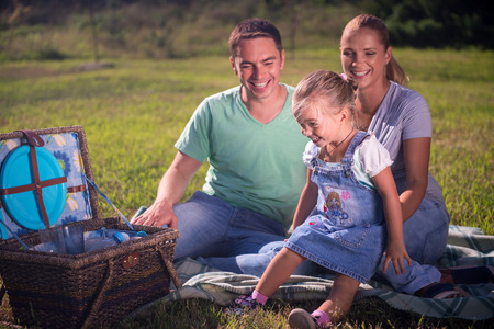 Full-length portrait of lovely mom, dad and little daughter sitting on the soft plaid near the wicker basket for picnic having fun photo