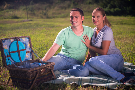 picnicking: Full-length portrait of lovely couple wearing T-shirts and jeans sitting on the plaid near the wicker basket for picnic looking at something and laughing