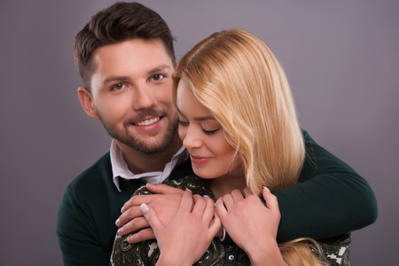 Half-length portrait of handsome young smiling man wearing white shirt and dark-green cardigan standing behind his beautiful fair-haired smiling girlfriend hugging wanted to kiss her. Isolated on dark background photo