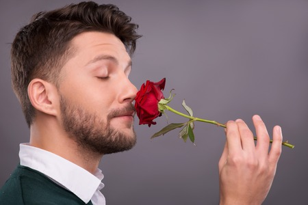 Half-length portrait of handsome young man holding a beautiful red rose wonderful gift for lover in his hands smelling it. Isolated on dark background photo