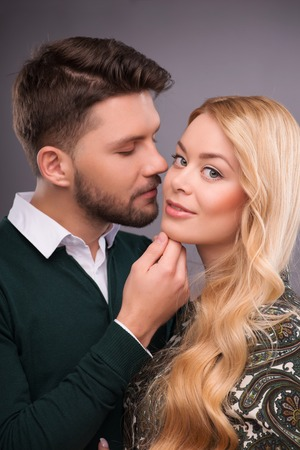 Half-length portrait of handsome young man wearing white shirt and dark-green cardigan standing hugging his beautiful fair-haired girlfriend wanted to kiss her photo