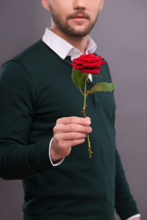 Selective focus on the beautiful red rose wonderful gift for lover in the hands of the man on background photo
