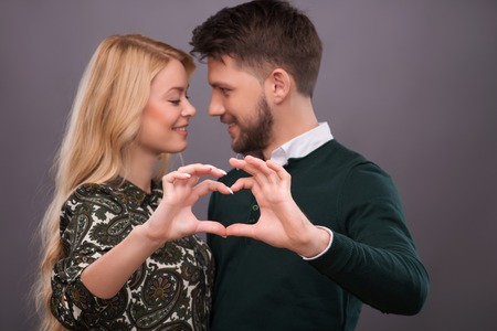 Selective focus on the hands making a form of little heart. Lovely smiling couple standing on background photo