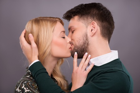 Half-length portrait of young beautiful couple standing with closed eyes facing each other kissing. Isolated on dark background photo
