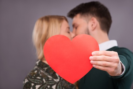 Selective focus on the big red heart in the hands of the lovely couple kissing on background photo