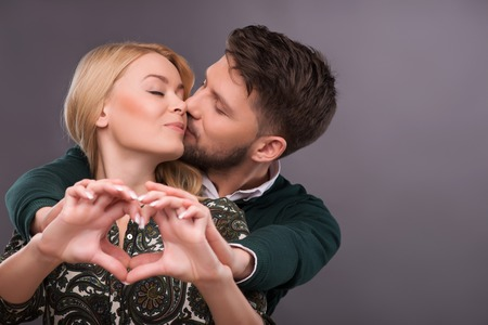 Selective focus on the of beautiful smiling couple standing together with closed eyes hugging each other making a form of little heart with their hands photo