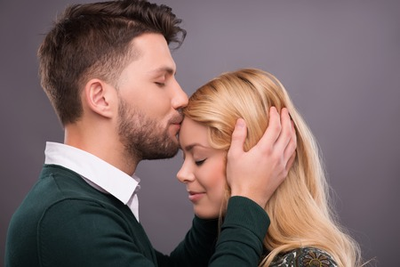 Half-length portrait of handsome smiling man wearing white shirt and green jumper standing aside kissing her beautiful happy girlfriend in the forehead. Isolated on dark background photo